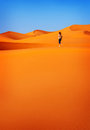 Woman in hot desert trekking along beautiful orange sandy dunes exploring sahara active vacation discovering nature concept Royalty Free Stock Photo