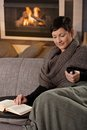 Woman with hot drink sitting on sofa at home on a cold winter day drinking tea looking down Royalty Free Stock Photos