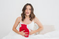 Woman with hot water rubber bag on stomach in bed young bottle sitting Royalty Free Stock Photo