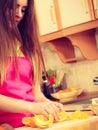 Woman housewife in kitchen cutting orange fruits