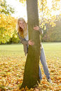 Woman huggging a tree laughing young hugging in autumn park Royalty Free Stock Images