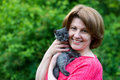 Woman hugging a blue kitten Scottish strait in outdoors Royalty Free Stock Photo