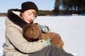 Woman hugging her dog shar pei while sitting on the snowy field near a pinery on a sunny day winter vaction concept training Royalty Free Stock Photo