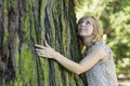 Woman hugging large tree trunk while looking up Stock Photography