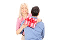Woman hugging a man and holding a present men isolated on white background Stock Images