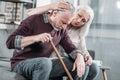 Woman hugging senior husband with walking stick at home Royalty Free Stock Photo