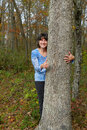 Woman hugging tree a expresses love of nature by a and giving thumbs up sign Royalty Free Stock Images