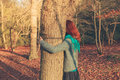 Woman hugging tree at sunset Royalty Free Stock Photo