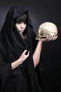 Woman with a human cranium in black Stock Images