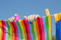 A woman hung washed laundry outdoors. Girl drying laundry on a clothes line in the sun in the outdoor