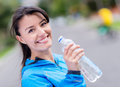 Woman hydrating after workout drinking water from a bottle Stock Photography