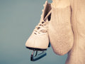 Woman with ice skates getting ready for ice skating carrying a pair of winter sport activity on blue Stock Photography