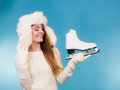 Woman with ice skates getting ready for ice skating winter sport activity smiling girl wearing warm clothing sweater and fur cap Stock Photography