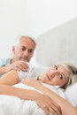Woman ignoring mature man in bed men while lying at the home Stock Photography
