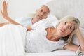 Woman ignoring mature man while lying in bed men at the home Royalty Free Stock Photo