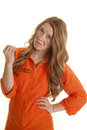 Woman inmate dirty hold up hand a in an orange jumpsuit looking at her finger nails Royalty Free Stock Photos