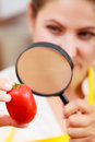 Woman inspecting tomato with magnifying glass. Royalty Free Stock Photo
