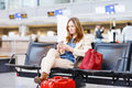 Woman at international airport waiting for flight at terminal Royalty Free Stock Photo
