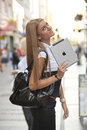 Woman with iPad tablet computer walking on street Stock Photography