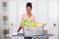 Woman With Iron And Clothes In Basket Royalty Free Stock Photo