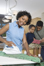 Woman Ironing Clothes With Family In Background Stock Photo