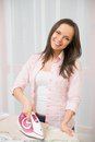Woman ironing clothes young cheerful in home interior Royalty Free Stock Images