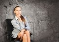 Woman in jacket, blouse sits on chair. Background Royalty Free Stock Photo