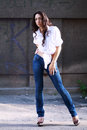 Woman in jeans posing stunning young outdoor over city wall Royalty Free Stock Images