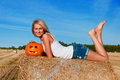 Woman in jeans shorts posing on a bale with pumpkin beautiful Royalty Free Stock Photo