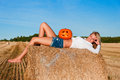 Woman in jeans shorts posing on a bale with pumpkin beautiful Royalty Free Stock Images