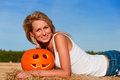 Woman in jeans shorts posing on a bale with pumpkin beautiful Royalty Free Stock Image