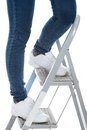 Woman in jeans on a step ladder isolated white Stock Photo
