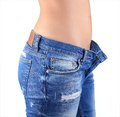 Woman jeans waist wearing weight loss stomach closeup skinny on a healthy slim fit body Royalty Free Stock Image