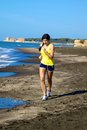 Woman jogging on the beach while listening music female model running exercising with castle background Stock Images