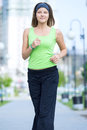 Woman jogging in city street park running at beautiful summer morning sport fitness model caucasian ethnicity training outdoor Stock Photography