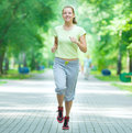 Woman jogging in city street park running at beautiful summer morning sport fitness model caucasian ethnicity training outdoor Royalty Free Stock Photos
