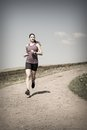 Woman jogging down gravel road photo of a beautiful young running a Stock Images