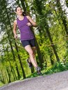 Woman jogging through the forest photo of a young and exercising on a gravel path a slight motion blur on jogger Royalty Free Stock Photography