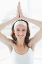 Woman with joined hands over head at bright fitness studio portrait of a smiling young Royalty Free Stock Image