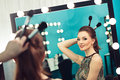 Woman joking in front of a mirror young beautiful with make up brushes Stock Photography