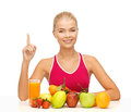 Woman with juice and fruits holding finger up young organic food or Royalty Free Stock Photo