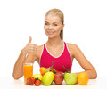 Woman with juice and fruits showing thumbs up young organic food or Royalty Free Stock Photos