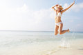 Woman jumping in the air on tropical beach into sea Royalty Free Stock Photo