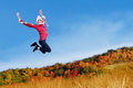 Woman jumping on the autumn park happy Stock Photo