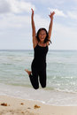 Woman jumping on the beach stock image Stock Photography