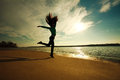 Woman jumping on the beach on sunny sky background Royalty Free Stock Photo