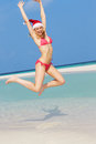 Woman jumping on beach wearing santa hat smiling Stock Photo
