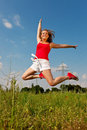 Woman jumping in front of power pole Stock Images