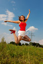 Woman jumping in front of power pole Royalty Free Stock Image