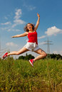 Woman jumping in front of power pole Stock Photo